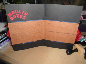 The inside of the Moulin Rouge card with the 'letterbox' cut-outs for the luggage tags to go into